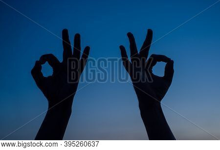 Sign Ok Silhouette. Two Man Hand Shows Sign Okay. Silhouette. Sign Okay. Ok.