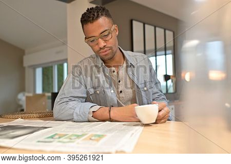 Handsmone cheerful guy reading newspaper and having coffee at home