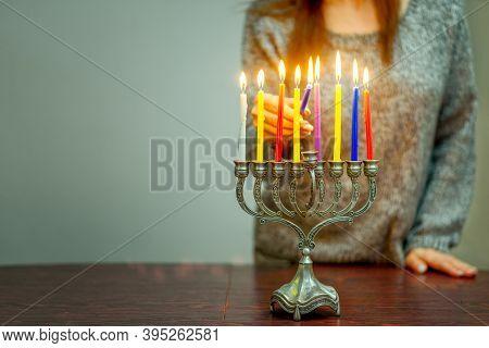 Jewish Woman Celebrating Holidays Hanukkah Alone Duringthe Covid-19 Pandemic. Woman Lighting Hanukka