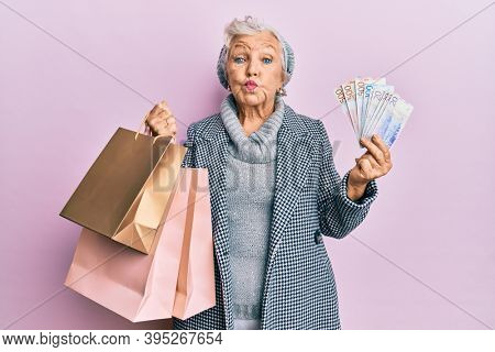 Senior grey-haired woman holding shopping bags and swedish krona banknotes puffing cheeks with funny face. mouth inflated with air, catching air.