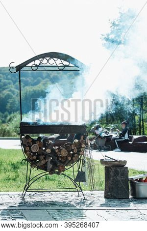 Flaming Log Wood In A Metal Outdoor Brazier With Ashes And Smoke In Rural Courtyard