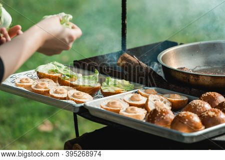 Chef Making Beef Burgers Outdoor On Food Festival Event. Street Food Ready To Serve On A Food Stall.