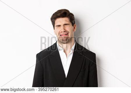 Close-up Of Miserable Man In Suit, Crying And Sobbing, Feeling Sad, Standing Against White Backgroun
