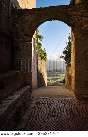 Medieval Old Town Narrow Street With An Antique Arch With A Picturesque Tuscany Hills Landscape View