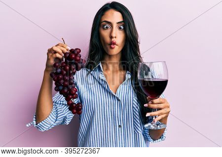 Beautiful hispanic woman holding branch of fresh grapes and red wine making fish face with mouth and squinting eyes, crazy and comical.