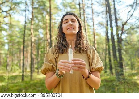 occult science and supernatural concept - young woman or witch with candle performing magic ritual in forest