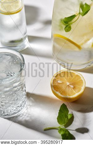 drink, detox and diet concept - glasses with fruit water or lemonade, lemon and peppermint on white table
