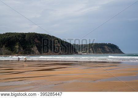 Rodiles, Asturias / Spain - 6 November 2020:  Woman Surfer Chicks Heading Into The Waves At Rodiles