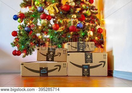 Calgary, Alberta, Canada. Nov. 16, 2020. Amazon Boxes Under A Christmas Tree With Ornaments And Ligh