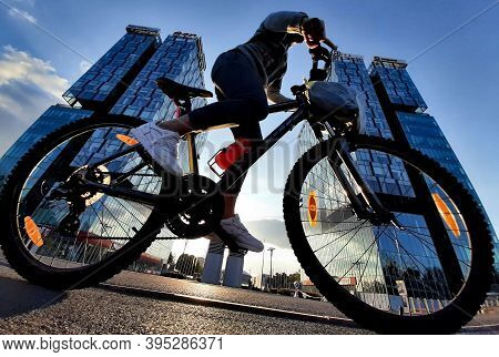 Bucharest, Romania - October 19, 2020: A Cyclist Rides A Bicycle In Front Of The City Gate Towers Si