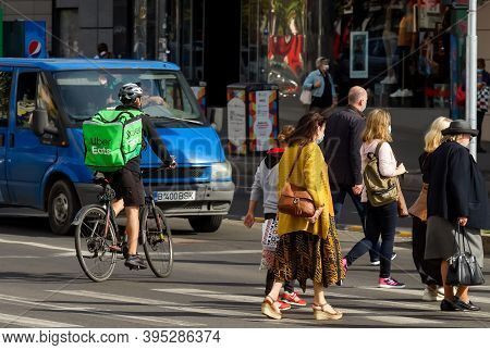 Bucharest, Romania - October 15, 2020: An Uber Eats Food Delivery Courier Delivers Food In Bucharest
