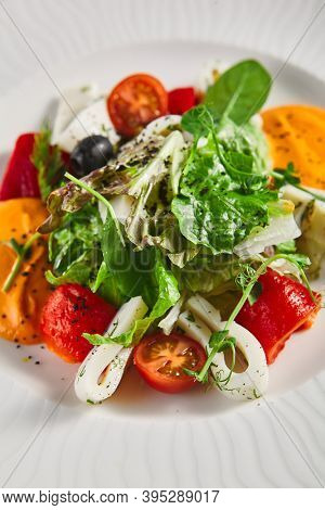 Roasted pepper salad with calamari and fresh greens. Rustic wooden table and grey textile