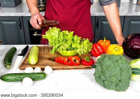 Hands Pour Olive Oil From Bottle On Green Salad Leaves. Vegetables, Cucumber, Pepper, Broccoli, Cabb