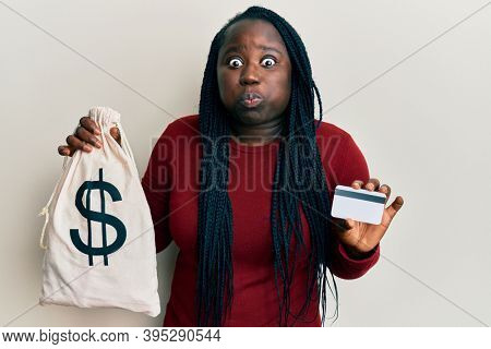 Young black woman with braids holding dollars bag and credit card puffing cheeks with funny face. mouth inflated with air, catching air.