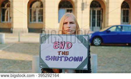 Concerned Woman With Protest Banner Calling To End Shutdown By Walking On The City Street