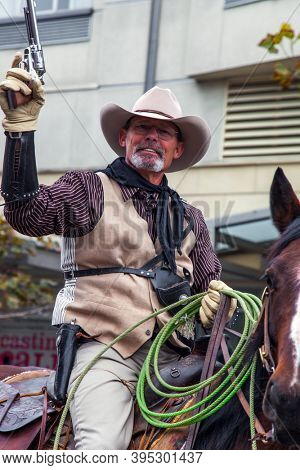 SAN FRANCISCO, USA - OCTOBER 11, 2009: Columbus Day celebration in San Francisco. Elderly cowboy with a fake old pistol and lasso rides a horse. Equestrian parade in honor of the holiday