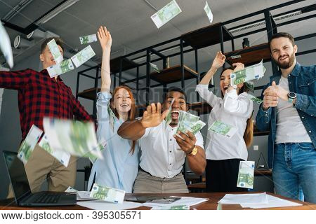 Low-angle Shot Of Cheerful Multi-ethnic Employees Celebrating Victory And Big Profit At Office Workp