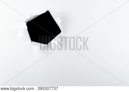 Black Hole In The Wall Of White Paper. Breakout Ripped A Big Black Hole In White Paper Round Hole In