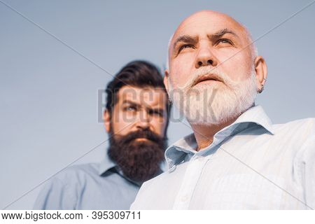 Happy Grandfather And Father Over Blue Sky And Clouds Background. Fatherhood. Father And Son Relaxin
