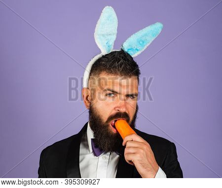 Easter Bunny Man Nibbles A Carrot Like A Hare. Healthy Man On Holiday. Easter Copy Space. Happy East