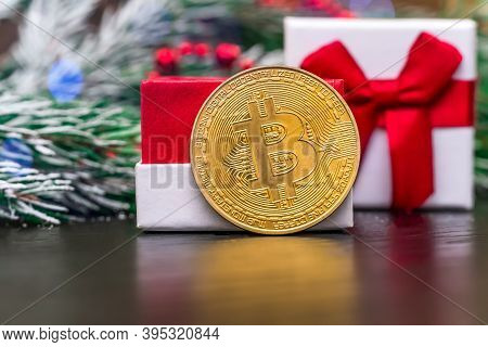 Gold Coin Bitcoin Stands Near The Gift Box On The Table Close-up On The Background Of A Spruce Branc