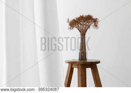 Bunch of dry papyrus plant in a glass vase on a wooden stool by a white curtain