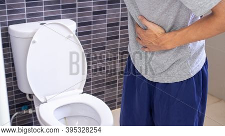 A Man Standing Has Diarrhea And Severely Toxic Food. Man Touch Belly In The Bathroom. Abdominal Pain