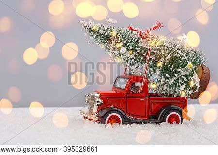 Red Small Retro Toy Truck With Sparkling Christmas Tree Lights On Truck Body On Blurred Background W