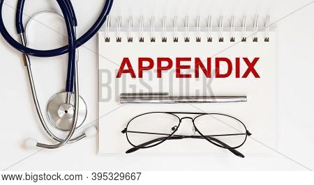 Stethoscope,glasses And Pen With Notepad With Text A Appendix On White Background