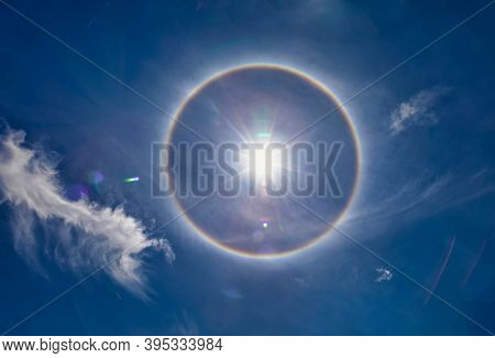 Halo is the optical phenomena produced by light interacting with ice crystals suspended in the atmosphere.  Among the best known halo is  the circular halo properly called the 22 degree  halo
