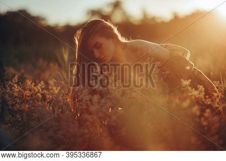 Young Happy Woman Sits, Enjoys And Sniffs Wildflowers In Dress In Meadow At Sunset. Backlit.