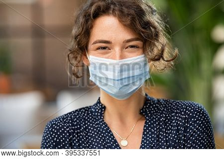 Portrait of happy young woman wearing face medical mask. Hopeful girl with protective face mask looking at camera. Smiling woman wearing safety protective mask to fight against covid-19 pandemic.