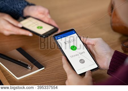 Close up hands holding mobile phone with app for send and receive money. Woman and customer holding smartphone and making payment transaction. Smart phone screen displaying digital payment sent.