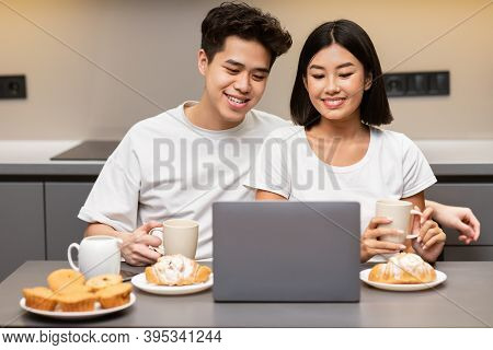 Asian Couple Watching Movie On Laptop In Kitchen Eating Pastry And Drinking Coffee Enjoying Tasty Br