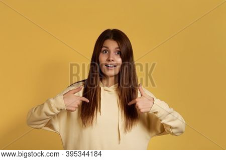 Confident Cheerful Caucasian Woman In Yellow Hoodie Looks Amazed, Points At Herself, Cant Believe Yo