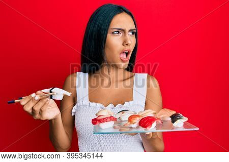 Young brunette woman eating butterfish sushi using chopsticks angry and mad screaming frustrated and furious, shouting with anger. rage and aggressive concept.