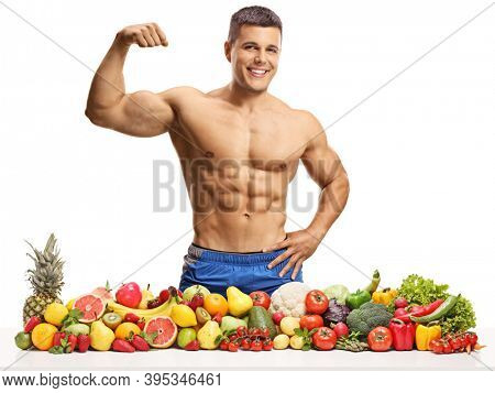 Topless muscular man showing flexing biceps muscle and posing with a pile of fruits and vegetables isolated on white background