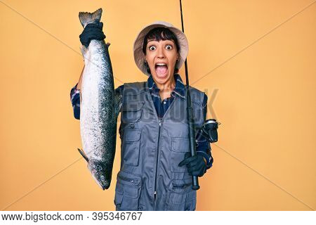 Beautiful brunettte fisher woman holding fishing rod and raw salmon celebrating crazy and amazed for success with open eyes screaming excited.