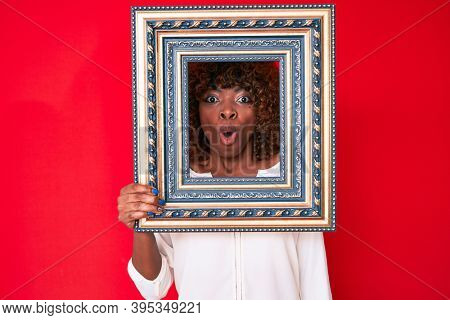 Young african american woman holding empty frame scared and amazed with open mouth for surprise, disbelief face