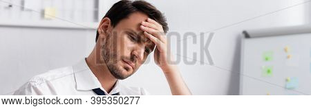 Businessman With Migraine Holding Hand On Forehead, While Looking Away On Blurred Background, Banner