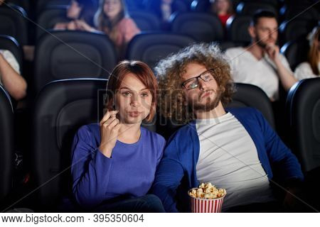 Selective Focus Of Young Caucasian Couple Watching Movie In Cinema, Sitting In Comfortable Black Sea