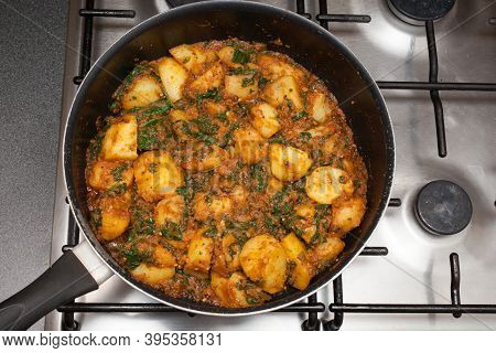 A Homemade Dish Of Sag Aloo, A Spicy Indian Potato And Spinach Dish Cooking In A Pan