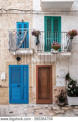 Entrance To Apartments, Balconies And Flowers. Closed Doors And Windows, Monopoli, Italy.