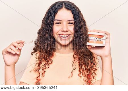 Adorable latin teenager smiling happy. Standing with smile on face holding denture with bracket and aligner over isolated white background