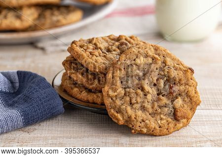 Closeup Of Oatmeal Raisin Cookies On Wooden Table With Glass Of Milk And Plate Of Cookies In Backgro