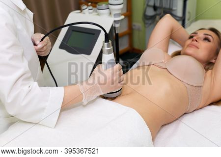 Young Beautiful Woman Lies On A Radiofrequency Lifting Procedure. The Beautician Of The Spa Salon Ho