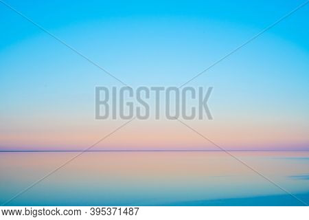Calm sea water against cloudless sundown sky in summer evening in countryside