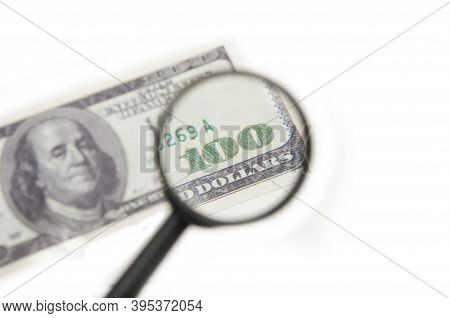 Magnifying Glass Magnifies The Number One Hundred On A Hundred Dollar Bill On A White Background