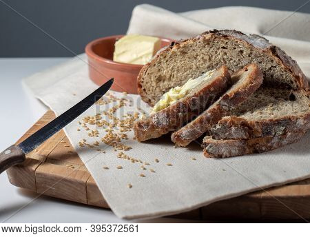 Homemade Baking. Round Sliced homemade Bread Is On A Wooden Board. The Butter Is In A Ceramic Plat