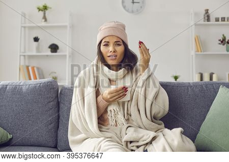 Sick Woman Wrapped In Plaid Sitting On Sofa, Sneezing And Talking To Ehealth Doctor